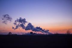 Rauchen Sie von der Fabrik, die in die Luft bei Sonnenuntergang steigt stockfoto