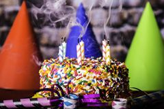 Rauchende Kerzen auf Geburtstags-Kuchen Stockbild
