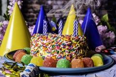 Rauchende Kerzen und Geburtstags-Kuchen Lizenzfreie Stockbilder