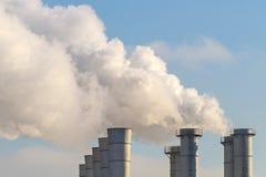 Rauchende Schlote auf Hintergrund des blauen Himmels als Illustration der Verschmutzung der Natur und des disbalance der Ökologie Stockbild