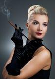 Rauchende Zigarette der reizend Dame Stockfoto