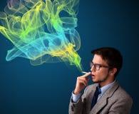 Rauchende Zigarette des gutaussehenden Mannes mit buntem Rauche Lizenzfreie Stockfotografie
