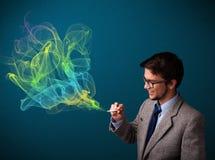 Rauchende Zigarette des gutaussehenden Mannes mit buntem Rauche Lizenzfreie Stockbilder