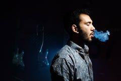 Rauchende Zigarette des jungen Mannes auf dunklem Hintergrund - rauchen Sie Ringe Stockfoto