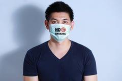 Rauchende Zigarette des jungen Mannes mit Schutzmaske Stockfotos