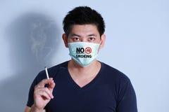 Rauchende Zigarette des jungen Mannes mit Schutzmaske Stockfotografie