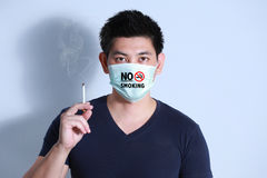 Rauchende Zigarette des jungen Mannes mit Schutzmaske Lizenzfreies Stockfoto