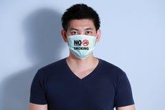 Rauchende Zigarette des jungen Mannes mit Schutzmaske Stockfoto
