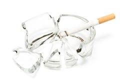Rauchende Zigarette in unterbrochenem Glasaschenbecher Stockfotografie