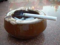 Rauchende Zigarettenkippe im Aschenbecher auf der Marmortabelle Stockbild