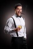 Rauchende Zigarre des jungen Kerls und trinkender Whisky Lizenzfreie Stockfotos