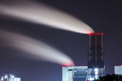 Rauchenden Schornsteinen bei Nacht - röka lampglaset på natten Arkivfoto