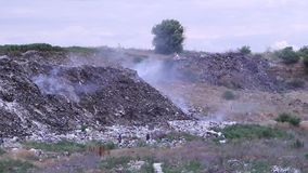 Rauchender Abfall auf Müllgrube Zwei arme Leute, die nützliche Sachen unter Hausmüll suchen stock footage