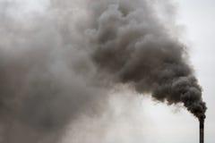 Rauchender Fabrikkamin, schwerer schwarzer Rauch auf dem Himmel Lizenzfreie Stockfotos