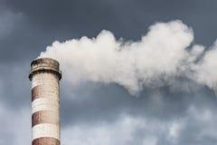 Rauchender Fabrikschornstein in den dunklen Wolken Konzept für Umweltschutz Stockfotos