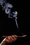 Rauchender Steuerknüppel in der Frau `s Hand stockfoto
