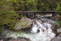 Rauchiger Gebirgswasserfall unter Brücke Stockfoto