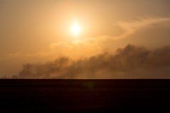 Rauchspalte vom Feuer bei Sonnenuntergang stockfotos