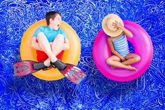 Raucous little boy and his quiet young sister stock photography