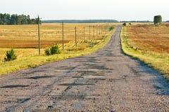 Raue gepflasterte Straße in einer Landschaft an einem sonnigen späten Nachmittag Lizenzfreies Stockfoto