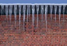 Raue Maurerarbeit der Backsteinmauer und große Eiszapfen Hintergrund Stockbild