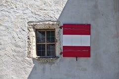 Raue vergipste Schlosswand mit dem Fenster und hölzernen Fensterläden gefärbt wie die österreichische Flagge, teils im Schatten Lizenzfreie Stockfotos