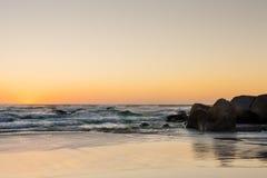 Raue Wellen bei Sonnenuntergang auf einem sandigen Strand mit Reflexionen auf dem w lizenzfreie stockfotos