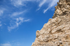 Rauer Felsen mit Graten und leichten Wolken, wie Federn auf einem blauen Himmel Lizenzfreie Stockfotos