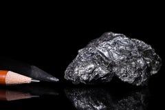 Rauer Graphit-Stein, Bleistiftführungen, schwarzer Hintergrund Lizenzfreies Stockbild
