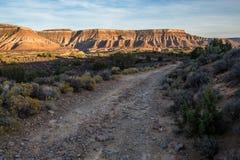 Rauer Schotterweg unterhalb der Wüsten-MESAs bei Sonnenuntergang Lizenzfreies Stockbild