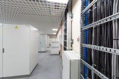 Raum mit Reihen von Gestellen mit Ausrüstung für Telekommunikation stockfoto