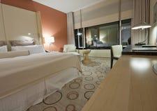 Raum mit Stuhllampen und -schreibtisch des king-size Betts Lizenzfreie Stockfotos