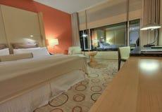 Raum mit Stuhllampen und -schreibtisch des king-size Betts Lizenzfreie Stockbilder