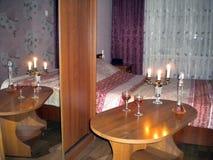 Raum mit Tabelle des gedämpften Lichts mit Kerzen und Weinbrand lizenzfreie stockbilder