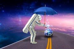 Raumfahrer mit Regenschirm und Planet Erde stockfotografie