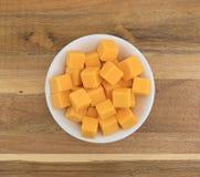 Rauminhalt berechneter milder Cheddar-Käse in einer weißen Schüssel Stockbild