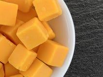 Rauminhalt berechneter milder Cheddar-Käse in einer weißen Schüssel Lizenzfreies Stockfoto