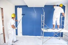 Raummaler malt eine Wand in einem neuen Haus Stockfotografie