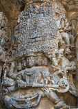 Ravana lifting Kailasha parvata and Shiva in turn pressing the mountain back to break the ego of Ravana; wall carving in Hoysalesh Stock Photo