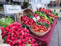 Ravanelli e peperoni su esposizione al mercato degli agricoltori di Corvallis, minerale metallifero Fotografia Stock