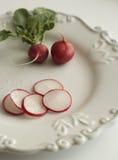 Ravanelli sul piatto bianco e vecchio Immagini Stock