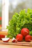 Ravanello e lattuga sulla tabella di cucina Immagine Stock Libera da Diritti