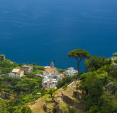 Ravello church and trees. Beautiful deep blue seas provide a contrast to the white church buildings on a Ravello cliff top on the Amalfi Coast Royalty Free Stock Image