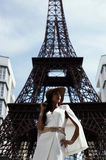 raven haired indian lady posing against fake Eiffel Tower Royalty Free Stock Photos