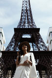 raven haired indian lady posing against fake Eiffel Tower Royalty Free Stock Image