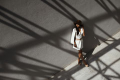 Raven haired indian lady posing in geometrical shadows of metal stractures Royalty Free Stock Photography