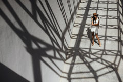 Raven haired indian lady posing in geometrical shadows of metal stractures Stock Photos
