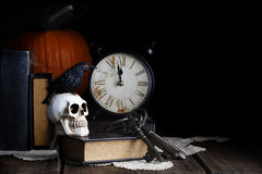 Raven Skull Midnight. A black raven with glowing orange eyes perched on human skull in dark library with old clock about to strike midnight. A concept for fun Stock Image