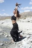 Raven Sorceress. Beautiful woman dressed in black holding raven feathers on a desert river shore Stock Image