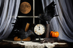 Ravens Midnight Full Moon. Two ravens with glowing orange eyes near clock about to strike midnight, rusty old lock and keys on desk with books and pumpkin. A Stock Image